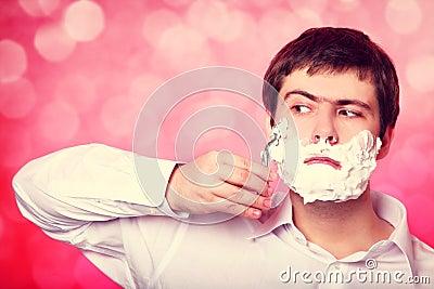 Man shaving  on red background