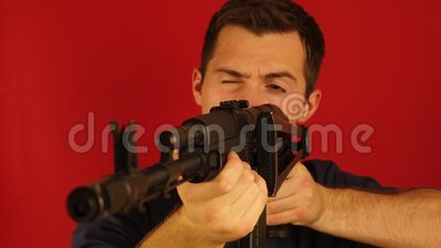 A man in a shirt on a red background. take aim with a black machine gun.  stock footage