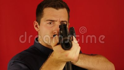 A man in a shirt on a red background. takes aim at the camera.  stock video