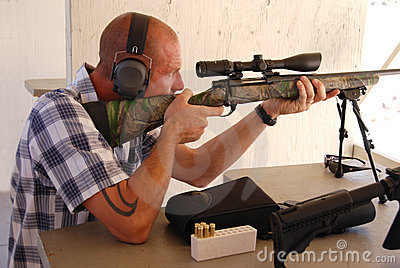 Man shooting sniper rifle.