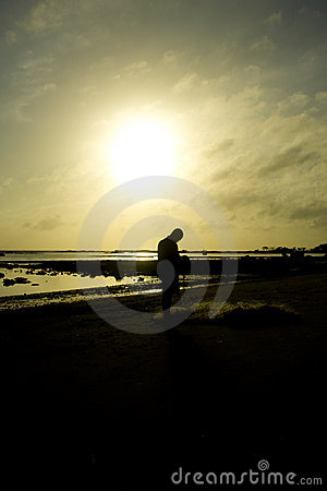 Man on shoreline at sunrise