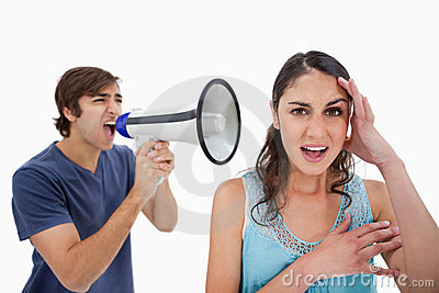 Man shouting at her girlfriend through a megaphone