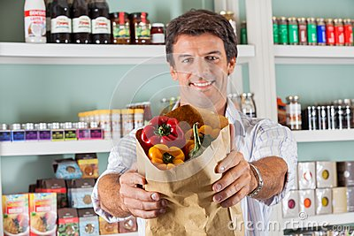 Man Showing Fresh Bellpeppers In Paper Bag