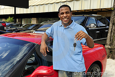 Man showing key of new red sports car