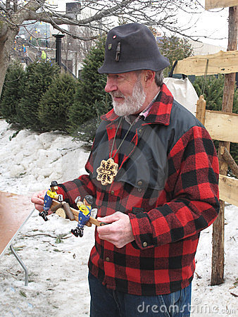 Man showing a wooden toy outside. Editorial Photography