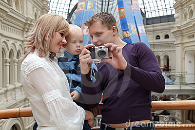 Man shows girl with baby picture with camera