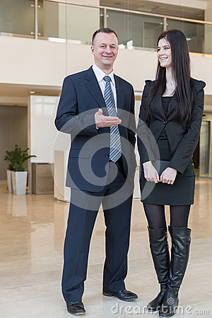 A man shows on woman with a notepad