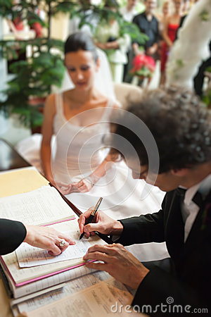 Man signing marriage papers