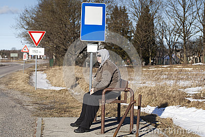 Man sits at a bus stop