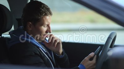 Man sits in car holding tablet with GPS navigator stock video footage