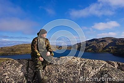 Man sits on a mountain top. Ridge Musta Tunturi.