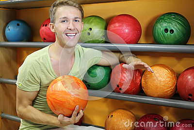 Man sits near shelves with balls in bowling club