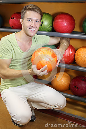 Man sits near shelves with balls and holds ball