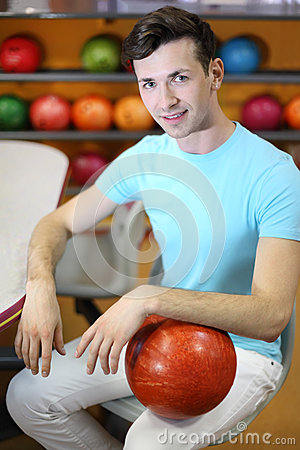 Man sits at table near shelves with balls