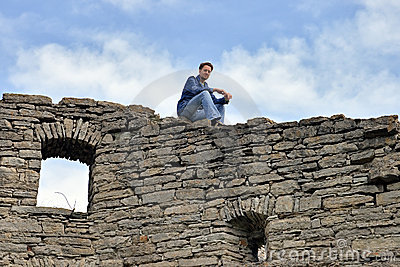 Man sits on the top old castle wall