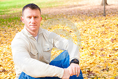 Man Sitting on Autumn Leaves