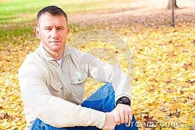 Man Sitting on Autumn Leaves