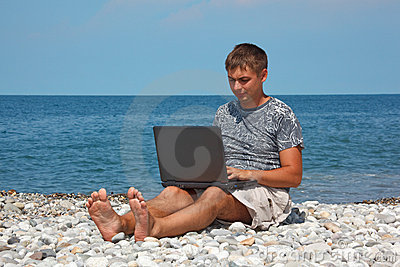 Man sitting on beach with laptop on his knees