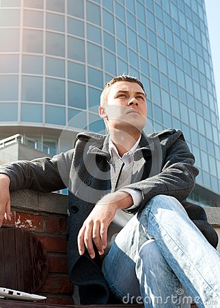Man sitting on a bench in front of a building