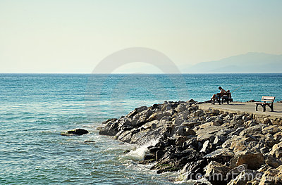 Man sitting on bench by sea, lateral view