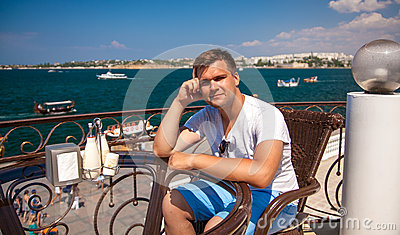 man sitting in cafe near sea