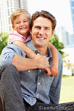Man sitting in city park with young son