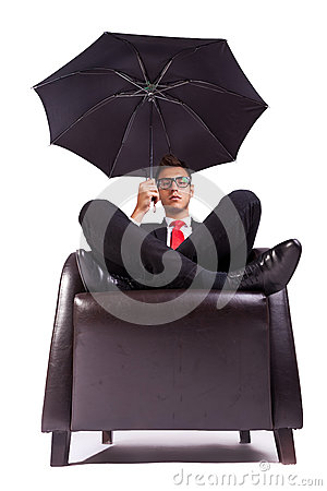 Man sitting in comfortable armchair with umbrella