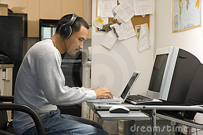 Man sitting at desk with computers.
