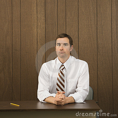 Man sitting at desk with pencil beside him.