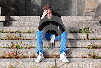 Man sitting down outside looks worried