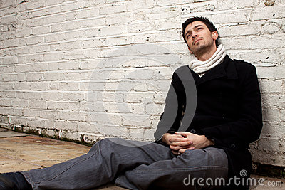 Man sitting on floor with back against wall