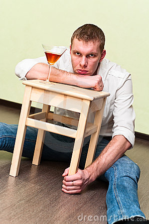Man sitting on floor with glass of alcohol