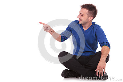Man sitting  on the floor and pointing to side