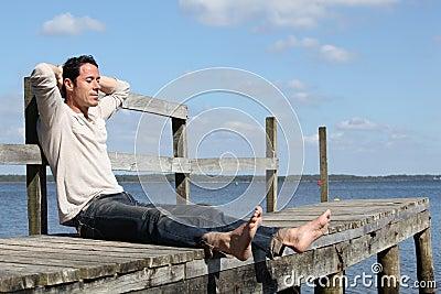 Man sitting on a jetty e