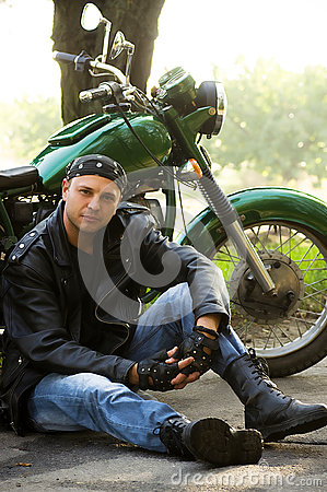 Man sitting by motorcycle