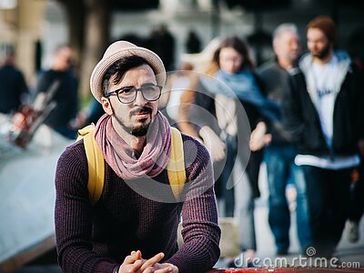 Man Sitting Next To Couple Of Person Walking On The Street During Daytime Free Public Domain Cc0 Image