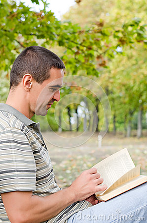 Man sitting outdoors reading a novel