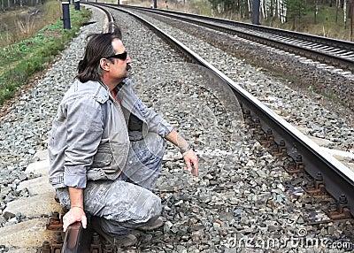 Man sitting on rail tracks