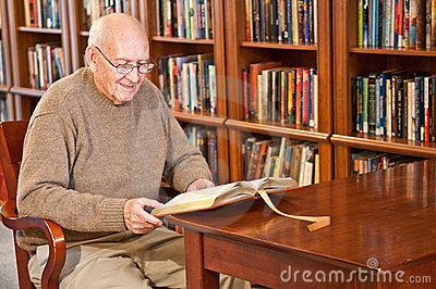Man Sitting and Reading Book at Library Table