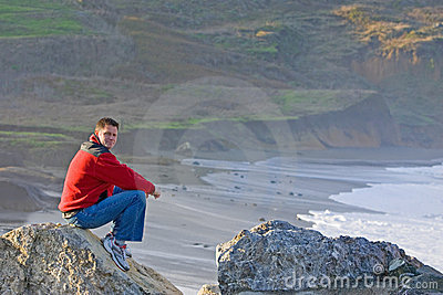 Man Sitting on Rocky Beach