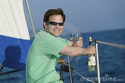 Man sitting on sailboat, drinking white wine