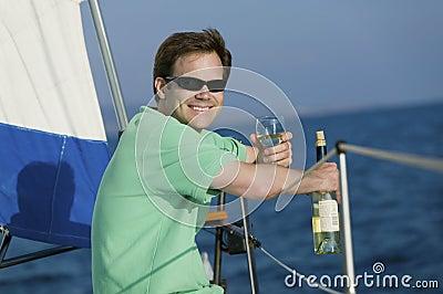 Man sitting on sailboat, drinking white wine