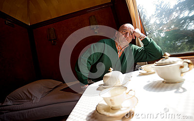 Man sitting sleeping wagon in train