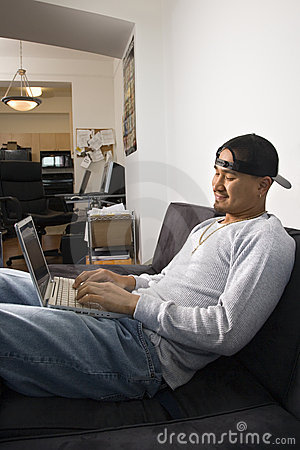 Man sitting on sofa using laptop.