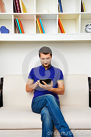 Man sitting on sofa and using tablet pc