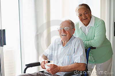 Man sitting on the wheelchair assisted by wife