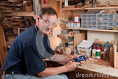 Man sitting at workbench in workshop