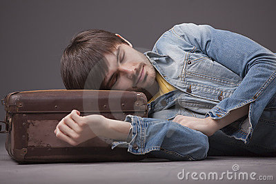 Man sleeping on suitcase