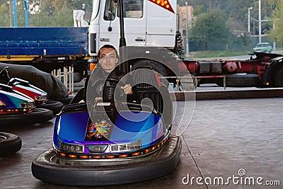 Man in small car at amusement park