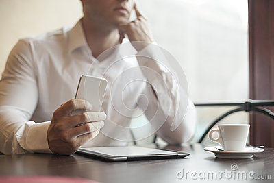 Businesman with smartphone in cafe